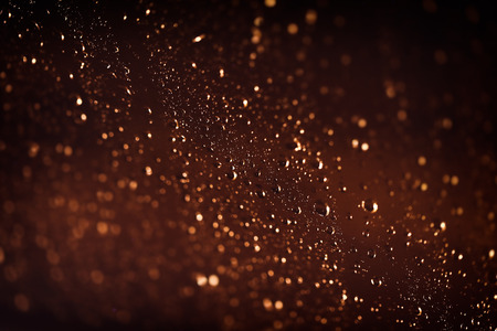 Brown background with water drops, rainy weather at night, rain drops on the window, abstract textured wallpaper, autumn season concept Stock Photo