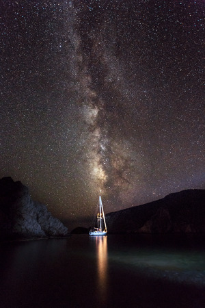 Amazing landscape of beautiful bright milky way on night starry sky, romantic traveling on sailboat at night, gorgeous nature view   版權商用圖片