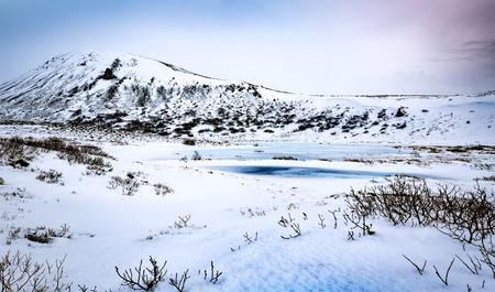 美しい冬の風景、その背後にある小さな凍った湖と雄大な山々の素晴らしいパノラマビュー、アイスランドへの極端な旅行 写真素材
