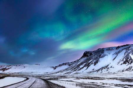 Beautiful landscape of the northern lights over hight mountains covered with snow,  Aurora Borealis, wonderful phenomena of nature, winter time in Budir, Iceland   版權商用圖片