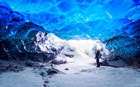 Podróżnik w jaskini lodowej, człowiek stojący pod ziemią w lodowcu, specyficzny klimat, Park Narodowy Vatnajökull, niesamowita przyroda Skaftafell, Islandia