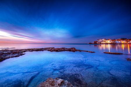 夕暮れ時の沿岸都市、バトゥーンと地中海の景色、夜の家々からの光、バトゥーンはレバノン北部の沿岸都市であり、世界で最も古い都市の一つで 写真素材