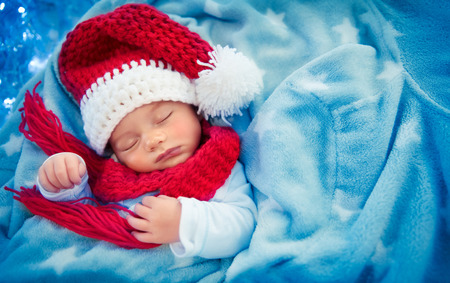 Portrait of a cute little baby boy wearing festive Santa hat and sleeping at home, covered with his blue blanket like in snow, happy Christmas holidays  Stock Photo