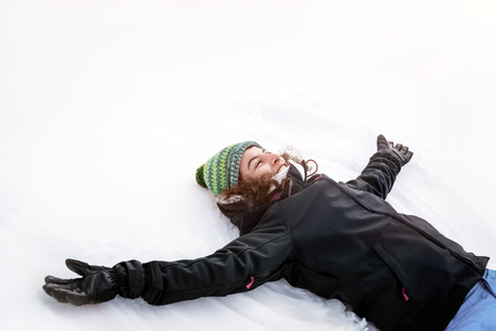 Joyful cheerful girl lying down on the white clean snow with raised up hands and making snow angel, enjoying snowy weather, happy winter holidays