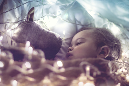 Sweet little baby boy sleeping with favourite soft toy, dreaming at home on magic night, vintage style fantasy photo  Imagens