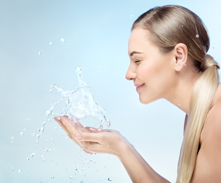 Profile portrait of a nice blond girl with pleasure washing her face in the morning by clear refreshing water, perfect clean skin, using anti acne remedy, hygiene concept Reklamní fotografie - 94533548