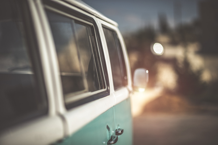 Cute old-fashioned campervan on the road, happy traveling on the retro bus, revival automobile of hippie, rare stylish blue car Stock Photo - 94285144