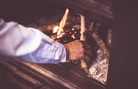 Man kindle a fire in the fireplace, grandpa making warmth and cozy atmosphere in the country house, romantic and peaceful winter evening  Stock Photo