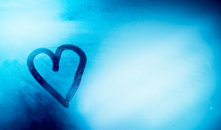 Love is in the air, heart shaped drawing on the misted-up window, abstract blue background, romantic winter holidays concept, happy Valentines day