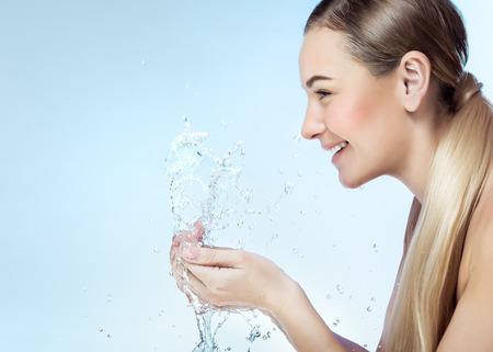 透明なさわやかな水、完璧なきれいな肌、抗にきびの治療薬を使用して、コピースペースと写真で朝に彼女の顔を洗う喜びを持つ素敵なブロンドの女の子のプロフィールの肖像画