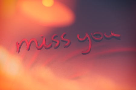 Handwritten phrase miss you on the window glass, abstract background, love and happiness on Valentines day holiday