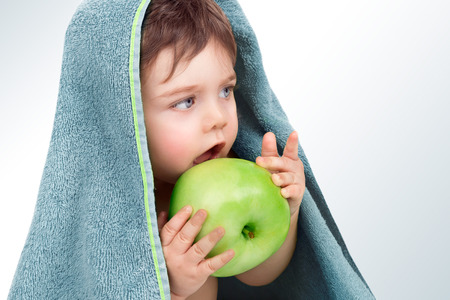 Closeup portrait of  a nice little baby boy after bath, sitting covered with grey towel and eating big green apple, healthy babies nutrition, hygiene and healthy lifestyle concept