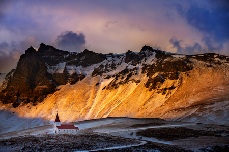 Iceland, beautiful sunset landscape of Vik Myrdal village, kurkirka church against the snowy mountains, South coast of Iceland