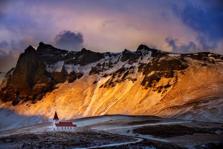 Iceland, beautiful sunset landscape of Vik Myrdal village, kurkirka church against the snowy mountains, South coast of Iceland