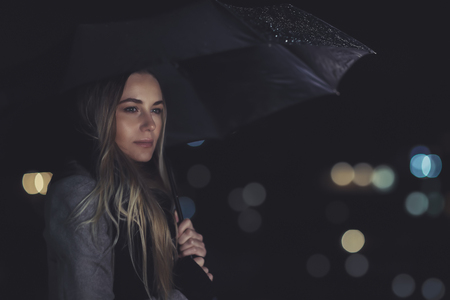 Fashion portrait of beautiful gorgeous woman standing with umbrella under the rain over night city lights background, melancholy concept