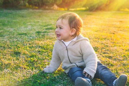 Neonato sveglio all'aperto, piccolo bambino dolce che si siede sul campo di erba verde fresco nel giorno soleggiato luminoso, godente dei primi giorni di primavera, infanzia spensierata felice