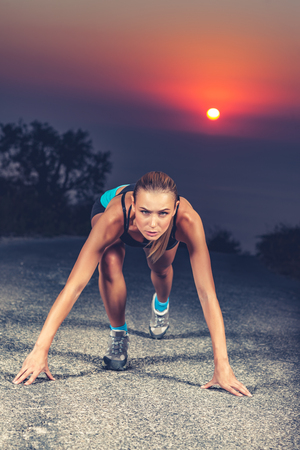 Sprinter woman on the start, preparing to run, training for athletic competition, evening workout outdoors over beautiful sunset background, the concept of hard work and willpower Stock Photo
