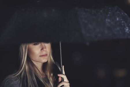 Portrait of a gorgeous sad woman standing under big black umbrella in rainy night, loneliness and sadness concept