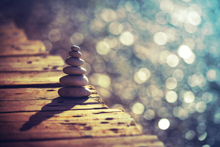 Paix intérieure et équilibre, tas de galets sur le pont en bois sur la plage, vacances d'été sur la station thermale, concept de vie et d'harmonie