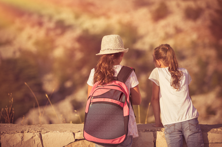 Summer camp adventures, two little girls best friends enjoying mountains hike, schoolchildren on outdoor tour, happy summer holidays in the camp Stock Photo