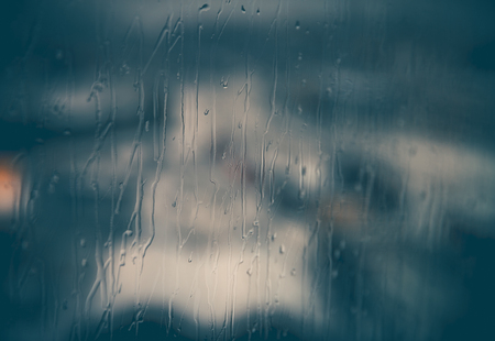Abstract rainy window background, rain drops streaming down on glass, cold season, sadness concept