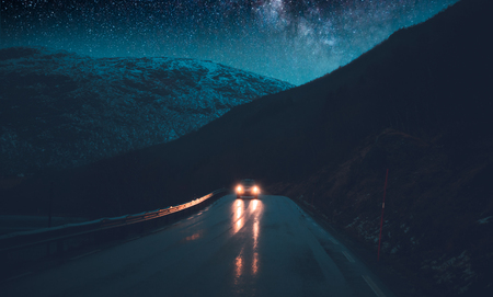 Norway adventures, night road trip under the stars, traveling in the car at nighttime, driving along hight snowy mountains, freedom concept