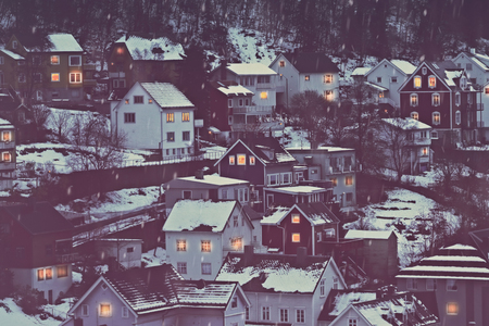 Norway, beautiful city covered with snow, wintertime cityscape, many little houses with glowing windows in the evening, Narvik, Scandinavia, Europe