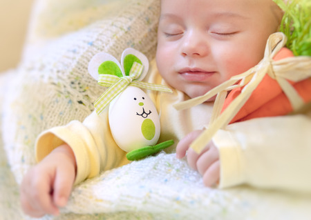 Portrait of a cute little baby boy sleeping in his bed at home with decorated egg-bunny toy, traditional Easter symbol, happy Easter, spring holiday