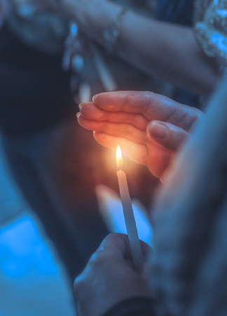 Believer in a church with candle, closeup photo of a woman covers the flame of the candle with her hand, asks for help from God on the Easter holiday