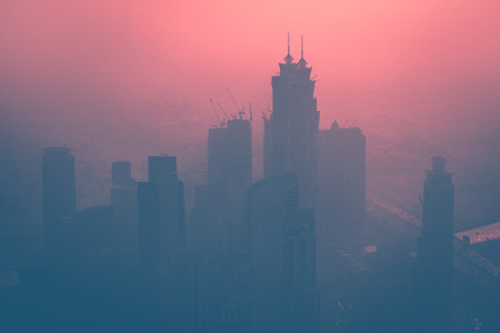 Dubai at dusk, cityscape with high-rise towers in the fog over beautiful pink sunset background