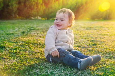 Cute baby boy outdoors, sweet little child sitting on fresh green grass field in bright sunny day, enjoying first spring days, happy carefree childhood
