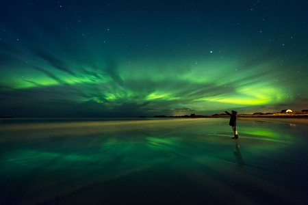 Amazing view on the northern lights, beautiful green lights on the sky at night, traveler woman enjoying Aurora, merry dancers, beautiful phenomenon in Norway  Фото со стока
