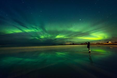 Splendida vista sull'aurora boreale, belle luci verdi sul cielo di notte, donna viaggiatore che si gode Aurora, allegri ballerini, bellissimo fenomeno in Norvegia Archivio Fotografico - 98880713
