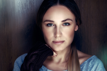 Authentic womens portrait, girl wearing natural makeupr, stands over brown wooden background, natural beauty of youth, healthy genuine appearance of young adult female