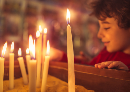 Little boy in the church on Easter, puts a candle to prays to God, enjoying happy religious holiday, good peaceful atmosphere in holy place