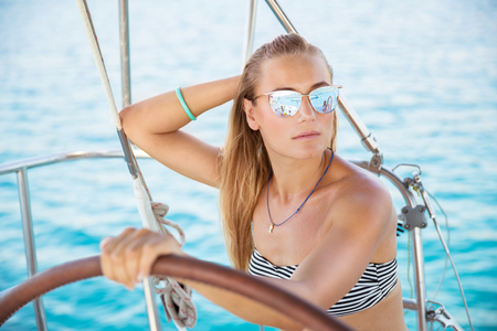 Portrait of an attractive girl on sailboat, wearing stylish sunglasses and bikini,  luxury summer vacation on the sea, active holidays