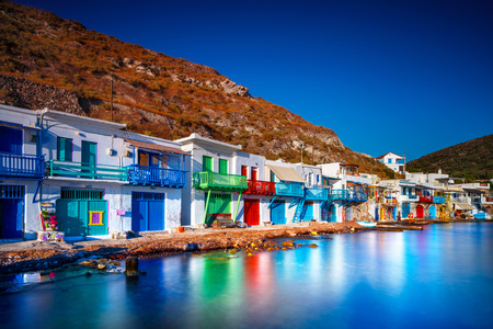 Colorful fisherman houses stand under the mountain on the aegean seashore,  summer on the beach of Milos, Greece, Europe