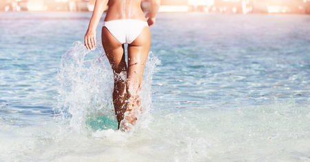Woman walking away along blue transparent water on the beach, body part of sportive slim female, summer vacation concept