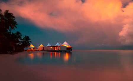 Romantic beach landscape, little restaurant on the bank of tropical island at the evening, summer vacation on a luxury resort, Maldives