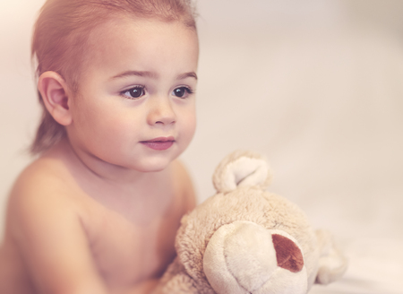Portrait of a cute little boy with soft bear toy at home, woke up after a dream with his best friend, happy carefree childhood