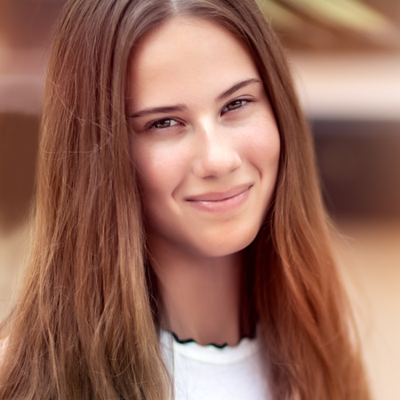 Closeup authentic womens portrait, genuine beauty of a young pretty girl with long natural hair, no makeup, happy healthy lifestyle of youth