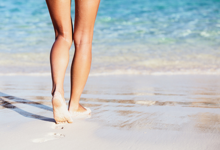 Woman walking into the sea, body part, perfect tanning womens legs, enjoying time on the beach, summer vacation concept