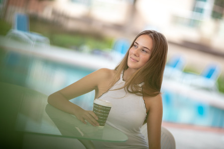 Pretty woman with morning coffee near poolside on the beach resort, enjoying summer vacation, peacefulness and relaxation concept