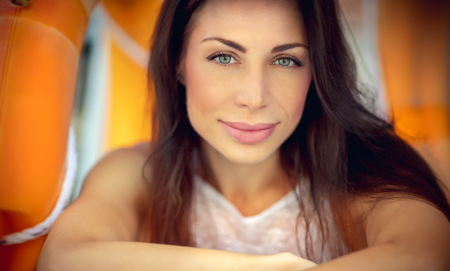 Closeup portrait of a beautiful brunette woman, authentic beauty of female with natural makeup, happy summer weekend in the park