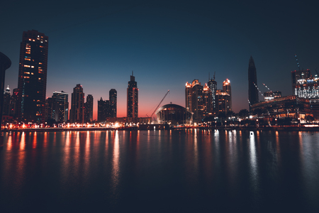 Dubai downtown at night, beautiful glowing lights from the towers reflected in the water, amazing nighttime cityscape