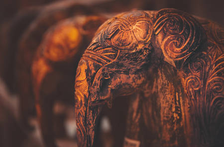 Grunge vintage style photo of a little wooden elephants with artistically carved drawings, traditional asian and african souvenir Imagens
