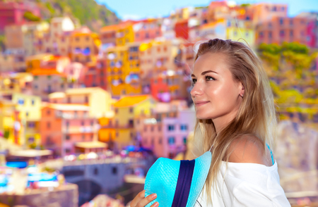 Portrait of a pretty traveler girl enjoying amazing view on a many colorful houses, active summer vacation, enjoying trip to Cinque Terre, Italy, Europe