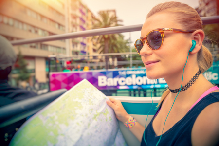 Cute blond woman riding on the bus with headphones in ears and with map in hands, discovering points of interest of Barcelona, active summer vacation in Europe Imagens - 103716947