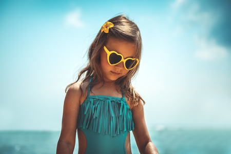 Portrait of a cute little girl on the beach, enjoying happy summer vacation, stylish beach look of a young girl, kids fashion Standard-Bild