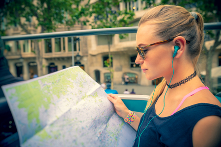Pretty girl enjoying bus tour in Europe, exploring map and listening stories about famous places of Barcelona, happy active summer vacation, Spain Banco de Imagens